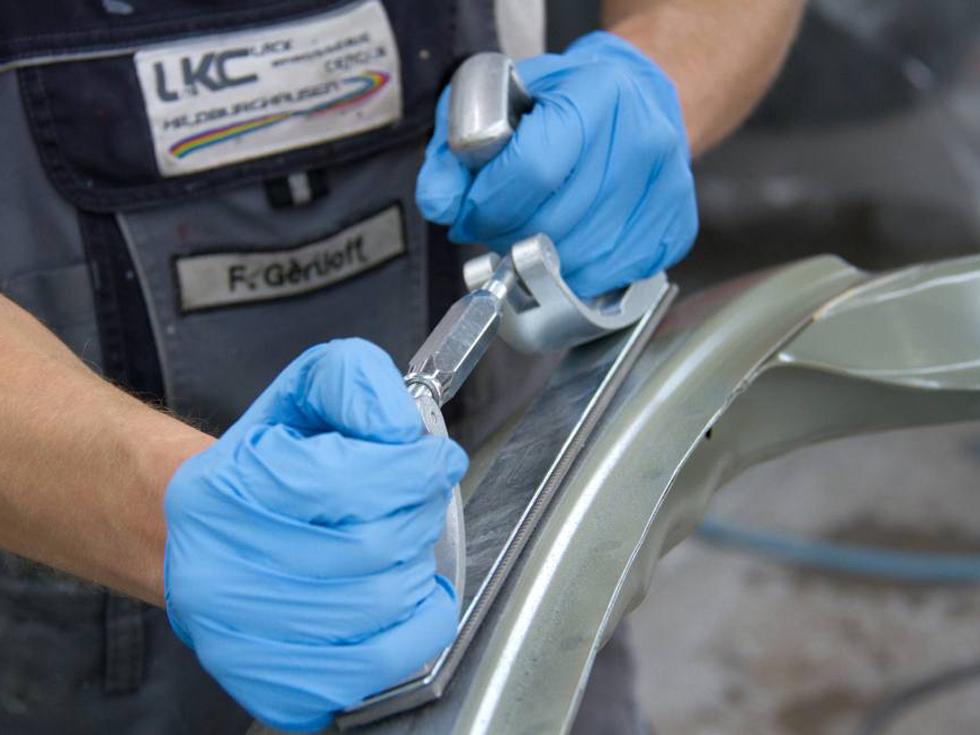 KFZ-Mechaniker bei der Fahrzeugaufbereitung beim Abschleifen eines KFZ-Teils
